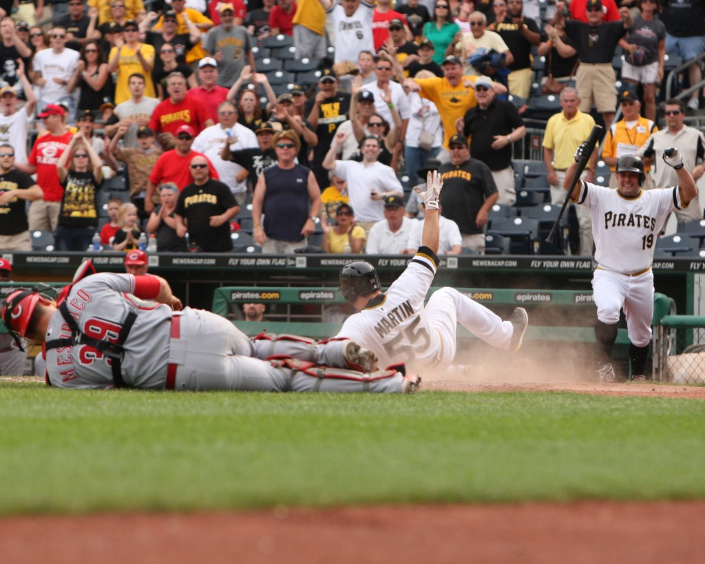 Russell Martin slides past catcher Devin Mesoraco to score the game-winning run in the 11th inning.